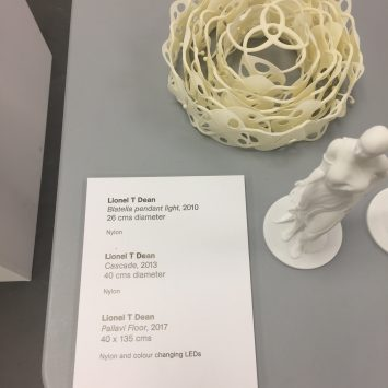 A reference sheet next to 3D printed statues