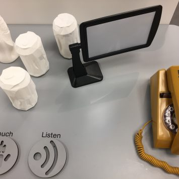 A collection of 3D printed objects on a table with a mustard-yellow trim phone and magnifying glass