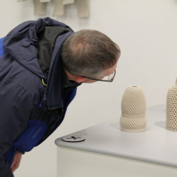 A man examines some 3D printed objects