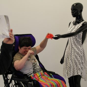A wheelchair bound woman takes an item from a mannequin's hand