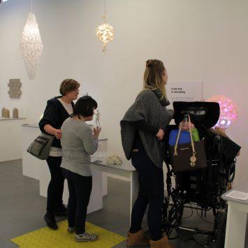 Several impaired visitors examine exhibits