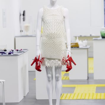 A mannequin wearing a cream 3D printed dress and holding red 3d printed heels