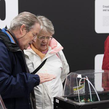 An older couple study an exhibit