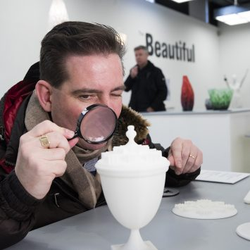 A man uses a magnifying glass to look at an exhibit