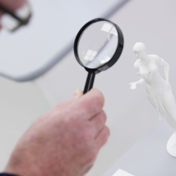Someone using a magnifying glass to examine a statue