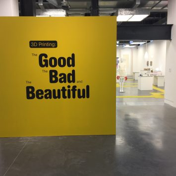 A large yellow wall with black text of the exhibition title
