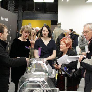 Visitors examining several 3D printers