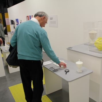 A man touches an exhibit on a table